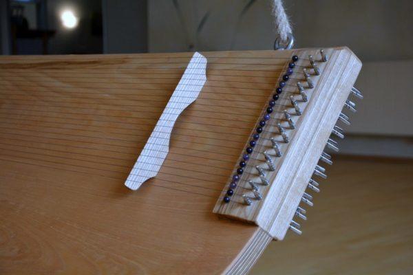 Klang-Schaukel 4 Spielflächen Saitenwirbel, jede Spielfläche hat einen beweglichen Steg